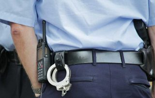 Torso of a police officer from behind with a radio and handcuffs attached to his belt performing a traffic stop