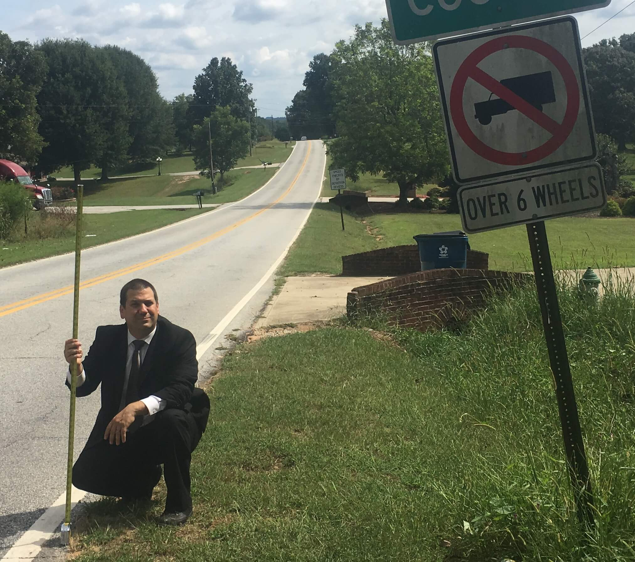 Traffic Sign Ticket Attorney Sean Goldstein measuring traffic sign height for client defense in Barrow County