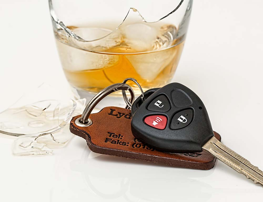Car keys in front of a broken glass of liquor leading to a DUI in Metro Atlanta.